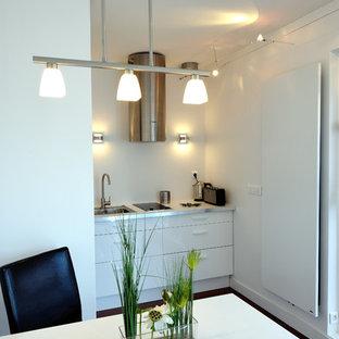 Aménagement d'une cuisine américaine linéaire contemporaine de taille moyenne avec des portes de placard blanches et aucun îlot.