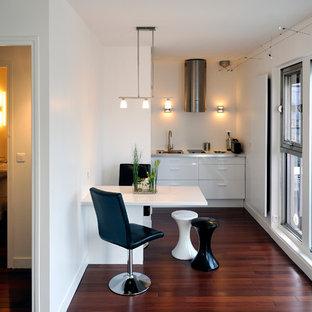 Réalisation d'une petite cuisine américaine linéaire design avec un évier posé, un placard à porte plane, des portes de placard blanches, un plan de travail en inox, un électroménager encastrable, un sol en bois foncé et aucun îlot.