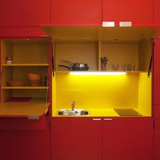 Idées déco pour une petite cuisine linéaire contemporaine fermée avec un évier 1 bac, des portes de placard rouges, une crédence jaune, aucun îlot et un plan de travail jaune.