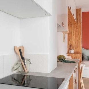 Свежая идея для дизайна: маленькая отдельная, прямая кухня в современном стиле с врезной раковиной, плоскими фасадами, белыми фасадами, столешницей из ламината, белым фартуком, фартуком из керамической плитки, техникой из нержавеющей стали, полом из цементной плитки, синим полом и серой столешницей - отличное фото интерьера