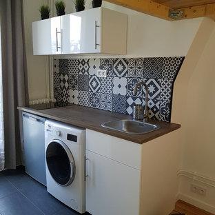 パリの小さいコンテンポラリースタイルのおしゃれなキッチン (シングルシンク、フラットパネル扉のキャビネット、白いキャビネット、ラミネートカウンター、黒いキッチンパネル、セメントタイルのキッチンパネル、白い調理設備、セラミックタイルの床、アイランドなし、黒い床) の写真