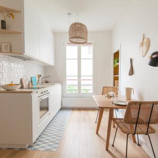 Aménagement d'une petit cuisine ouverte linéaire scandinave avec un évier 1 bac, un plan de travail en stratifié, une crédence blanche, un électroménager blanc et aucun îlot.