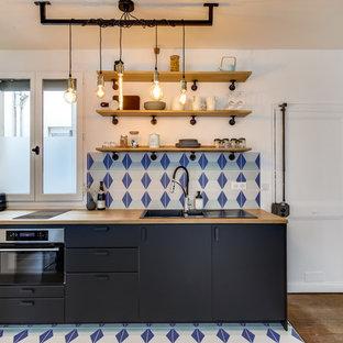 Réalisation d'une petit cuisine ouverte linéaire bohème avec un évier 2 bacs, des portes de placard noires, un plan de travail en bois, une crédence multicolore, une crédence en carrelage de pierre, un électroménager encastrable, un sol en carrelage de céramique et un sol multicolore.