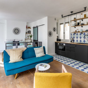 Inspiration for a small midcentury single-wall open plan kitchen in Paris with a double-bowl sink, black cabinets, wood benchtops, multi-coloured splashback, stone tile splashback, panelled appliances, ceramic floors and multi-coloured floor.