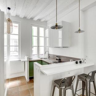Geschlossene Skandinavische Küche in U-Form mit Einbauwaschbecken, flächenbündigen Schrankfronten, grünen Schränken, Arbeitsplatte aus Holz, schwarzen Elektrogeräten, Halbinsel, beigem Boden und brauner Arbeitsplatte in Paris