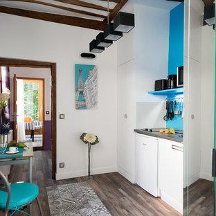 Idées déco pour une petite cuisine américaine linéaire contemporaine avec des portes de placard blanches.
