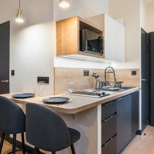Design ideas for a small single-wall eat-in kitchen in Lyon with an undermount sink, black cabinets, laminate benchtops, beige splashback, timber splashback, black appliances, light hardwood floors, beige floor and beige benchtop.
