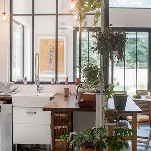 Cette image montre une cuisine urbaine en L fermée et de taille moyenne avec un évier de ferme, un plan de travail en bois, une crédence blanche, un sol en carrelage de céramique et aucun îlot.