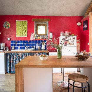 Aménagement d'une cuisine éclectique avec un évier posé, une crédence bleue, une crédence en carreau de céramique, un électroménager blanc, un sol en bois brun, un îlot central et un plan de travail en bois.