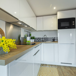Mid-sized contemporary l-shaped kitchen in Nice with a drop-in sink, white cabinets, wood benchtops, metallic splashback, metal splashback, black appliances, medium hardwood floors and no island.