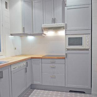 パリの中サイズのミッドセンチュリースタイルのおしゃれなキッチン (アンダーカウンターシンク、フラットパネル扉のキャビネット、グレーのキャビネット、木材カウンター、白いキッチンパネル、クッションフロア、アイランドなし) の写真