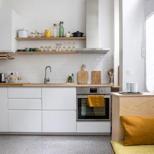 Exemple d'une petit cuisine ouverte linéaire tendance avec un évier posé, un placard à porte plane, des portes de placard blanches, un plan de travail en bois, une crédence blanche, une crédence en carrelage métro, un électroménager en acier inoxydable, aucun îlot, un sol gris et un plan de travail beige.