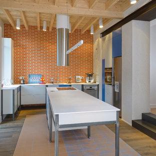 Idées déco pour une cuisine américaine industrielle en L avec un placard à porte plane, des portes de placard blanches, une crédence en brique, un électroménager en acier inoxydable, un îlot central, une crédence marron et un sol en bois clair.
