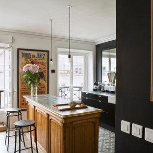 Réalisation d'une cuisine ouverte parallèle design de taille moyenne avec des portes de placard noires, un sol en ardoise et un îlot central.
