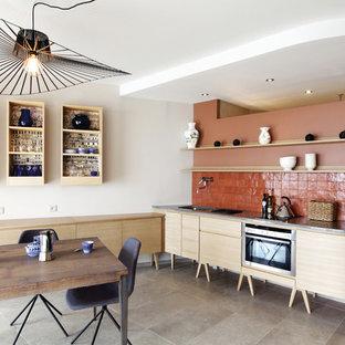 Réalisation d'une cuisine américaine design en L de taille moyenne avec un évier encastré, un placard à porte plane, des portes de placard en bois clair, une crédence orange, une crédence en carreau de terre cuite et aucun îlot.