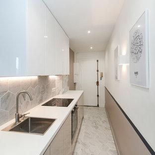 Exemple d'une cuisine linéaire tendance avec un évier posé, un placard à porte plane, des portes de placard beiges, une crédence grise, un électroménager noir, aucun îlot, un sol gris et un plan de travail blanc.