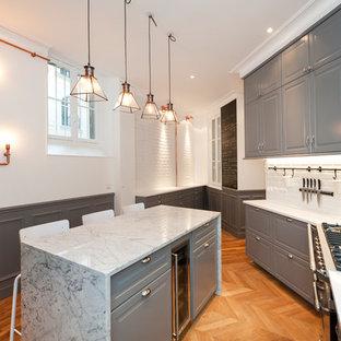 Exemple d'une cuisine chic avec un placard avec porte à panneau surélevé, des portes de placard grises, une crédence blanche, une crédence en carrelage métro, un sol en bois clair, un îlot central, un sol beige et un plan de travail blanc.