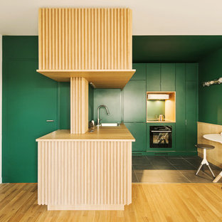 Photo of a contemporary l-shaped kitchen in Paris with a drop-in sink, flat-panel cabinets, green cabinets, wood benchtops, green splashback, black appliances, a peninsula, grey floor and beige benchtop.