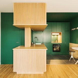 Idées déco pour une cuisine contemporaine en L avec un évier posé, un placard à porte plane, des portes de placards vertess, un plan de travail en bois, une crédence verte, un électroménager noir, une péninsule, un sol gris et un plan de travail beige.