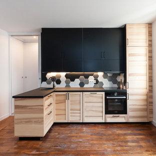 Cette photo montre une cuisine tendance en L de taille moyenne avec un évier posé, un placard à porte shaker, des portes de placard en bois clair, une crédence multicolore, un électroménager noir, un sol en bois brun, une péninsule, un sol marron et un plan de travail noir.