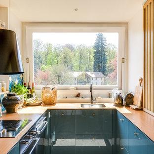 Cette photo montre une petite cuisine tendance en U avec un évier 1 bac, un placard à porte plane, des portes de placard bleues, un plan de travail en bois et une crédence multicolore.