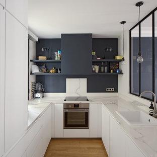Esempio di una cucina a U minimalista chiusa con lavello da incasso, ante lisce, ante bianche, elettrodomestici in acciaio inossidabile, pavimento in legno massello medio e pavimento marrone