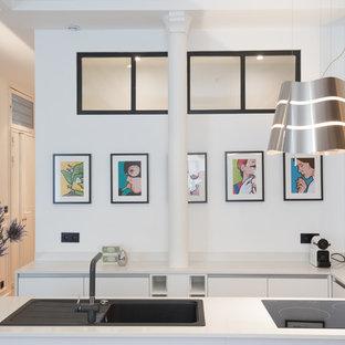 На фото: п-образная кухня в современном стиле с обеденным столом, одинарной раковиной, плоскими фасадами, белыми фасадами, столешницей из кварцита, белым фартуком, техникой из нержавеющей стали, полом из цементной плитки, островом, зеленым полом и белой столешницей