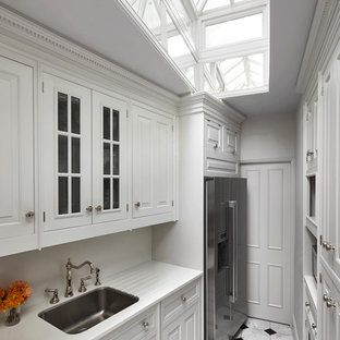This is an example of a small classic galley enclosed kitchen in London with a submerged sink, white cabinets, white splashback, stainless steel appliances, white floors, white worktops, raised-panel cabinets and no island.