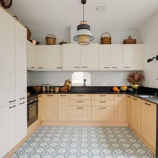 Exemple d'une cuisine ouverte chic en L avec un sol en carreaux de ciment, un plan de travail noir, un évier encastré, un placard à porte shaker, des portes de placard en bois clair, un électroménager en acier inoxydable, un sol bleu, un plan de travail en granite et une crédence en carreau de miroir.