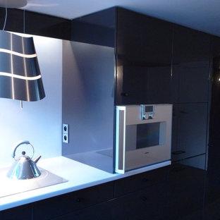 Idée de décoration pour une petit cuisine ouverte linéaire design avec un évier encastré, un placard à porte affleurante, des portes de placard violettes, un plan de travail en surface solide, une crédence bleue, un électroménager encastrable, un sol en bois clair et un plan de travail bleu.