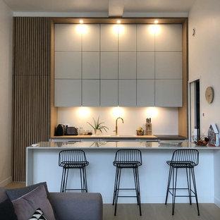 Idées déco pour une cuisine ouverte scandinave avec un placard à porte plane, des portes de placard grises, une crédence blanche, une péninsule, un sol en bois clair, un sol beige et un plan de travail gris.