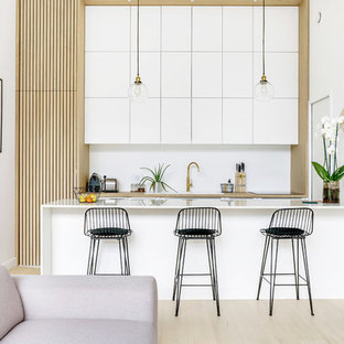 Inspiration for a scandinavian open plan kitchen in Paris with a drop-in sink, flat-panel cabinets, white cabinets, white splashback, light hardwood floors, a peninsula, beige floor and beige benchtop.