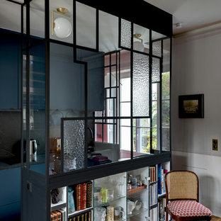 パリの小さいトランジショナルスタイルのおしゃれなキッチン (ドロップインシンク、インセット扉のキャビネット、青いキャビネット、タイルカウンター、黒いキッチンパネル、セラミックタイルのキッチンパネル、黒い調理設備、セメントタイルの床、アイランドなし、青い床) の写真