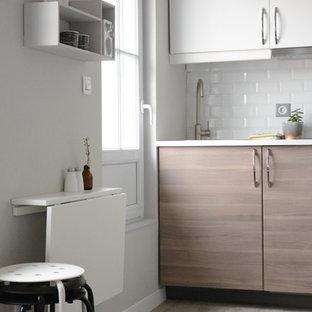 Diseño de cocina lineal, contemporánea, pequeña, sin isla, con puertas de armario de madera clara, salpicadero blanco y salpicadero de azulejos tipo metro