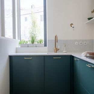 Modelo de cocina en L, tropical, con fregadero de un seno, armarios con paneles lisos, puertas de armario verdes, suelo de madera clara, suelo beige y encimeras grises
