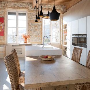 Cette image montre une cuisine ouverte méditerranéenne avec un évier 1 bac, un placard à porte plane, des portes de placard blanches, un électroménager noir, un îlot central, un sol gris et un plan de travail blanc.