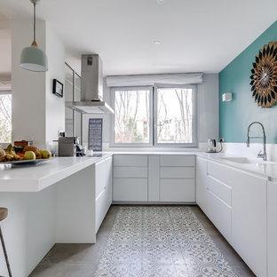 Aménagement d'une cuisine contemporaine en U avec un évier intégré, un placard à porte plane, des portes de placard blanches, une péninsule, un sol gris et un plan de travail blanc.