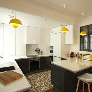 Réalisation d'une cuisine américaine design en L de taille moyenne avec des portes de placard blanches et une péninsule.
