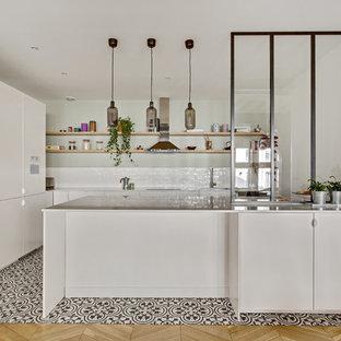 Exemple d'une cuisine américaine chic en L avec un évier encastré, un placard à porte plane, des portes de placard blanches, une crédence blanche, une crédence en carrelage métro, un électroménager en acier inoxydable, un sol en carreaux de ciment, une péninsule, un sol multicolore et un plan de travail blanc.