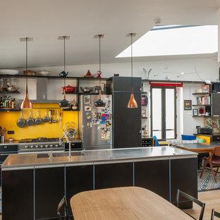 Exemple d'une grand cuisine ouverte parallèle éclectique avec des portes de placard noires, un îlot central, un évier intégré, une crédence jaune, un électroménager noir et un plan de travail gris.