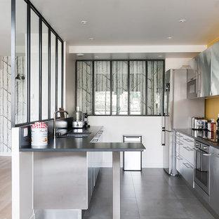 Cette photo montre une cuisine parallèle scandinave de taille moyenne et fermée avec un évier encastré, un placard à porte plane, une façade en inox, un électroménager en acier inoxydable, une péninsule et un sol en carrelage de céramique.