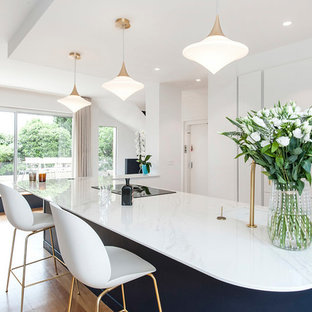 This is an example of a large contemporary galley eat-in kitchen in Paris with an integrated sink, flat-panel cabinets, white cabinets, with island and white benchtop.