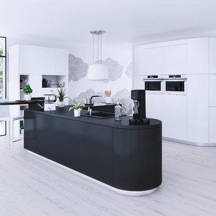 Offene, Einzeilige, Große Moderne Küche mit Waschbecken, weißen Schränken, Elektrogeräten mit Frontblende, hellem Holzboden und Kücheninsel in Paris