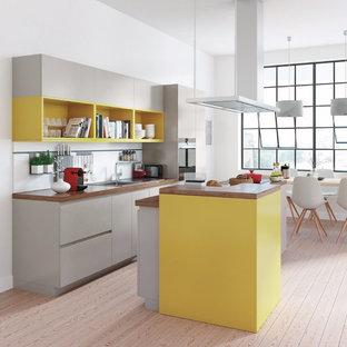 Idées déco pour une grande cuisine ouverte parallèle moderne avec un évier 1 bac, des portes de placard grises, un plan de travail en bois, un sol en bois clair et un îlot central.