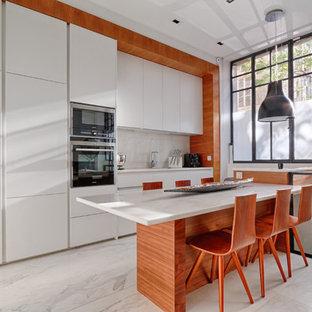 Aménagement d'une cuisine américaine linéaire contemporaine avec un placard à porte plane, des portes de placard blanches, une crédence blanche, un îlot central, un évier encastré et un plan de travail en marbre.