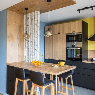 Exemple d'une cuisine américaine tendance en L de taille moyenne avec un plan de travail en bois, une crédence en bois, un îlot central et un sol gris.