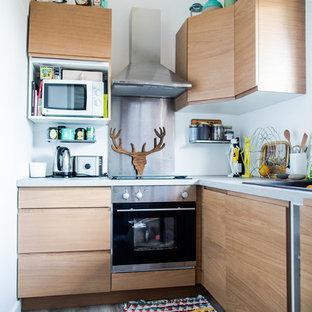 Diseño de cocina en L, actual, pequeña, cerrada, sin isla, con armarios con paneles con relieve, puertas de armario de madera clara, electrodomésticos de acero inoxidable, fregadero bajoencimera, encimera de acero inoxidable, salpicadero blanco y suelo de madera en tonos medios