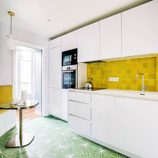 Mid-sized contemporary single-wall open plan kitchen in Paris with an undermount sink, flat-panel cabinets, white cabinets, quartzite benchtops, yellow splashback, terra-cotta splashback, panelled appliances, cement tiles, no island, green floor and white benchtop.