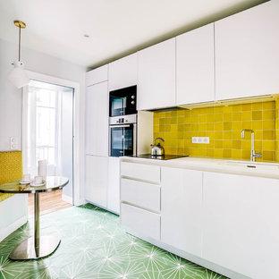 Exemple d'une cuisine ouverte linéaire tendance de taille moyenne avec un évier encastré, un placard à porte plane, des portes de placard blanches, un plan de travail en quartz, une crédence jaune, une crédence en carreau de terre cuite, un électroménager encastrable, un sol en carreaux de ciment, aucun îlot, un sol vert et un plan de travail blanc.