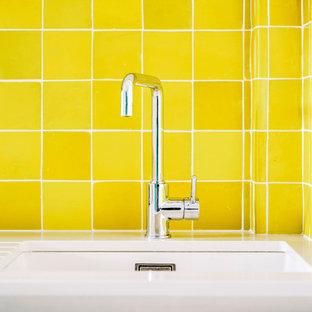 Создайте стильный интерьер: линейная кухня-гостиная среднего размера в стиле современная классика с врезной раковиной, плоскими фасадами, белыми фасадами, столешницей из кварцита, желтым фартуком, фартуком из терракотовой плитки, техникой под мебельный фасад, полом из цементной плитки, зеленым полом и белой столешницей без острова - последний тренд